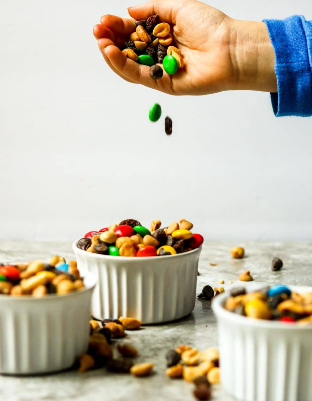 Monster Trail Mix spilling out of a hand into white bowls