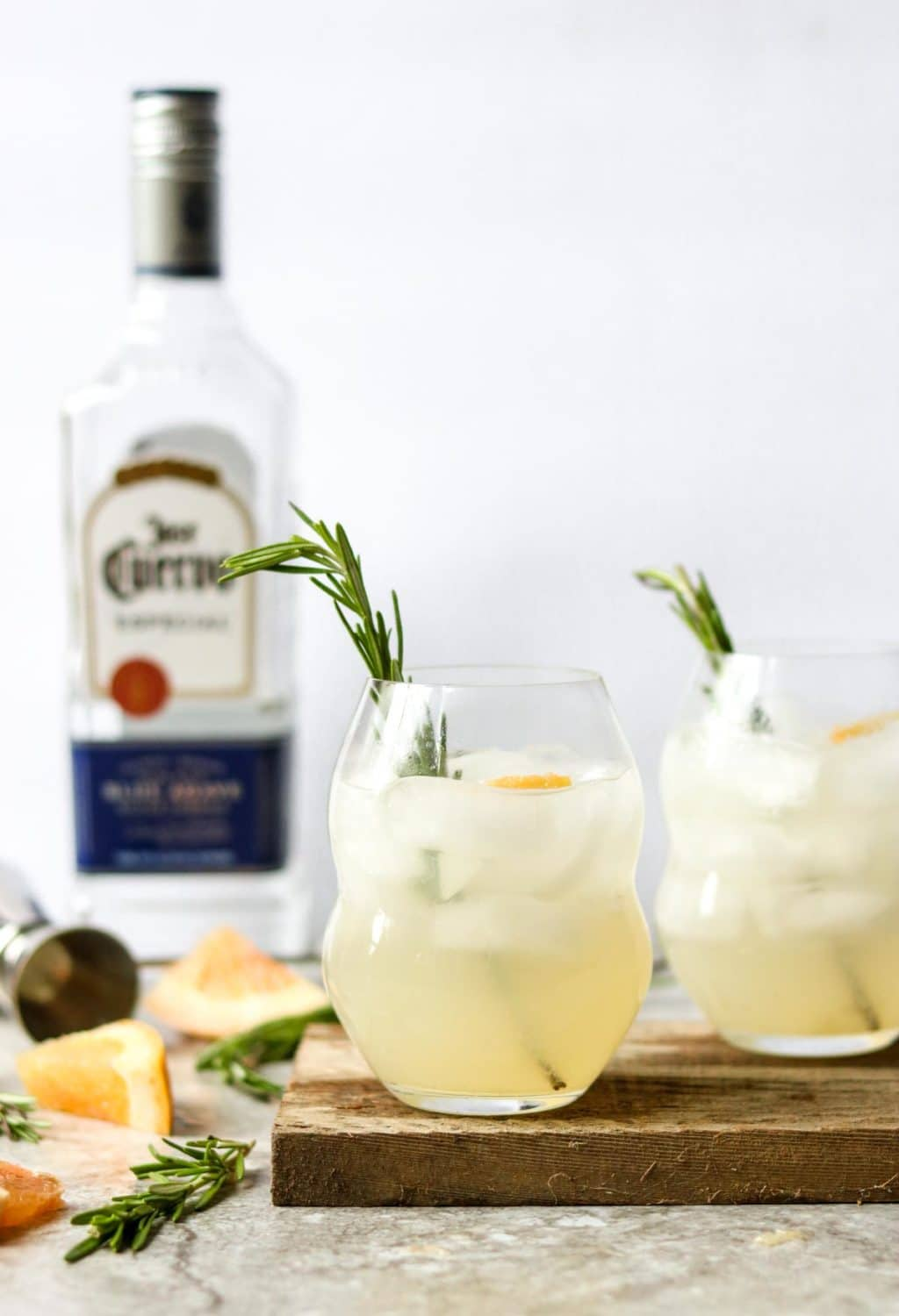 two glasses of Rosemary Paloma with rosemary sprig garnish, a bottle of tequila in the background