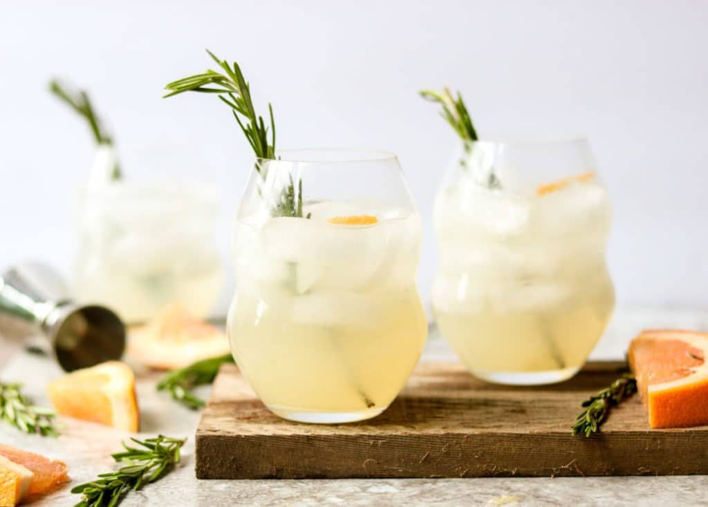 three glasses of paloma with fresh rosemary sprig garnish, rosemary and fresh grapefruit laying on the table