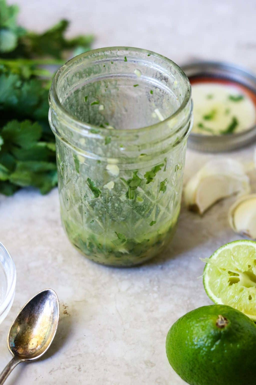 Cilantro Lime Vinaigrette in a mason jar with cilantro, garlic, and squeezed limes on the counter