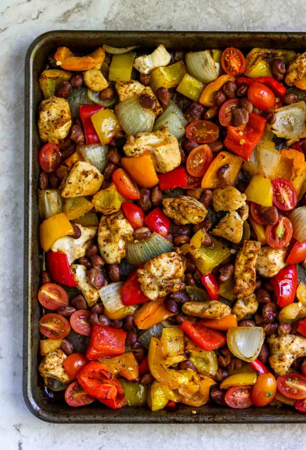 chicken and veggies seasoned with Mexican spices that have been cooked on a sheet pan