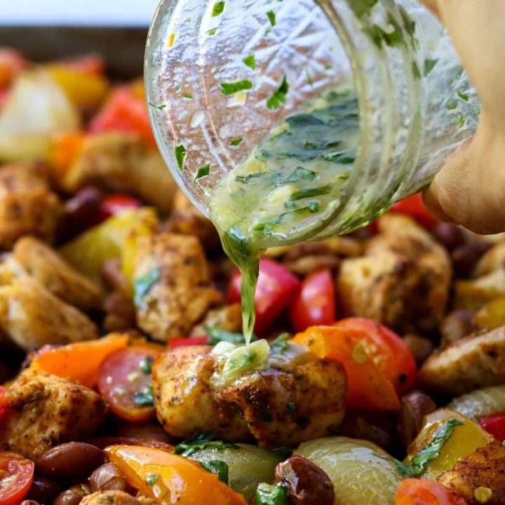 chicken fajita sheet pan dinner with cilantro lime vinaigrette being poured over the top