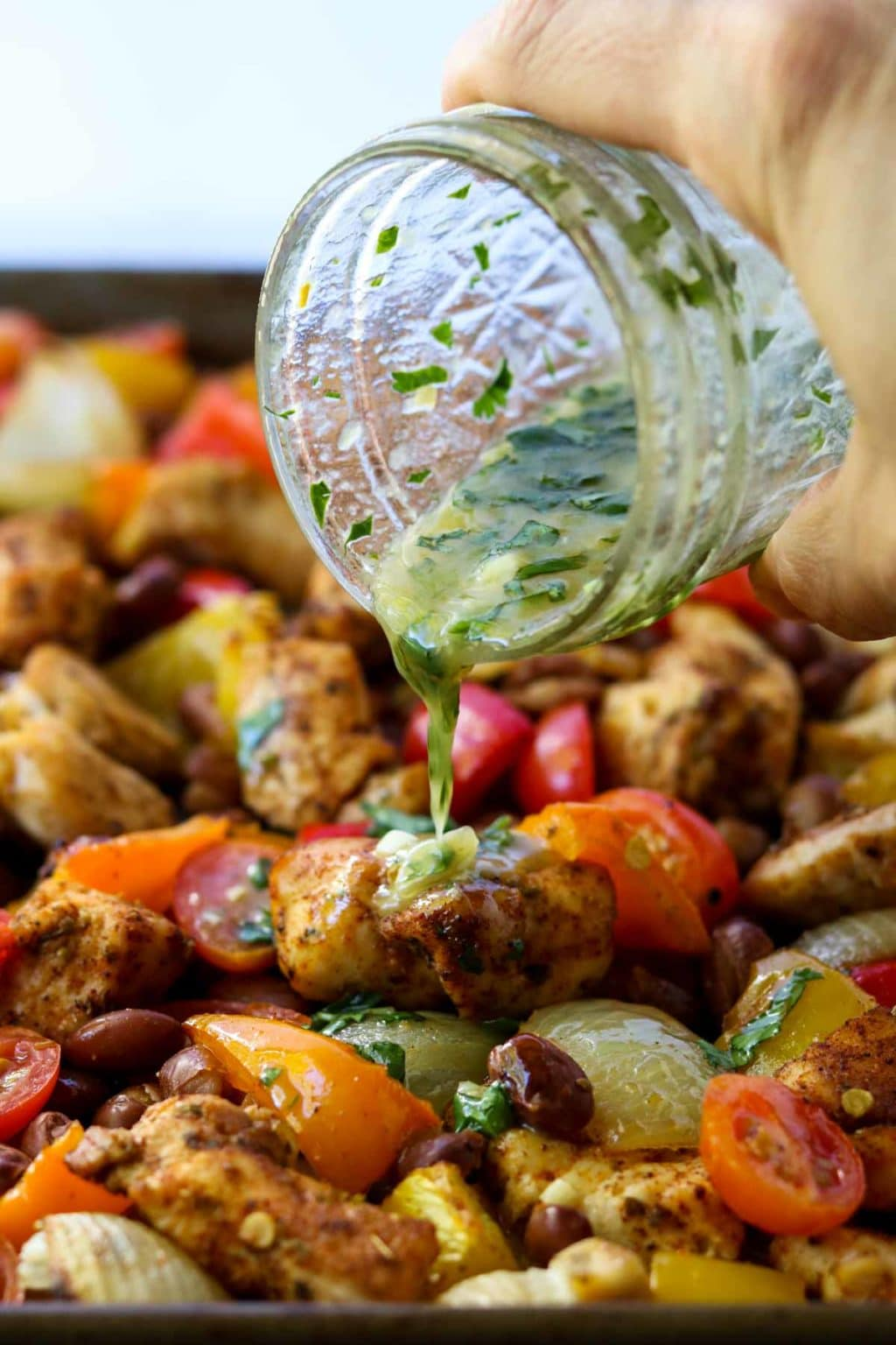 Chicken and veggies being drizzled with a cilantro lime vinaigrette