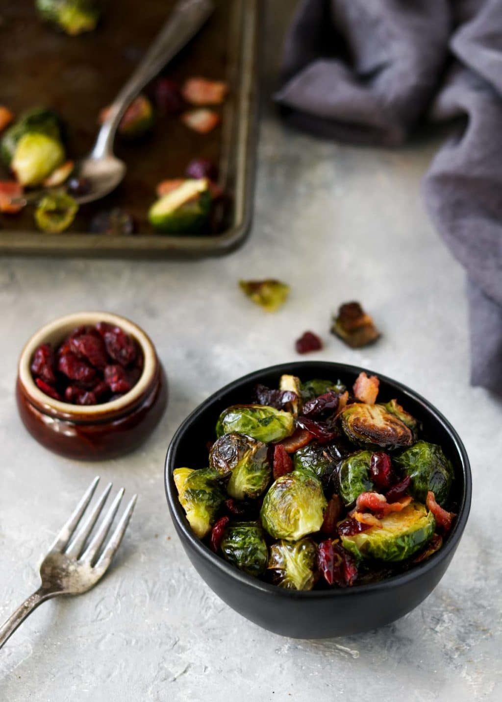 brussels sprouts in a black bowl with a cookie sheet in the background and a small bowl of dried cranberries