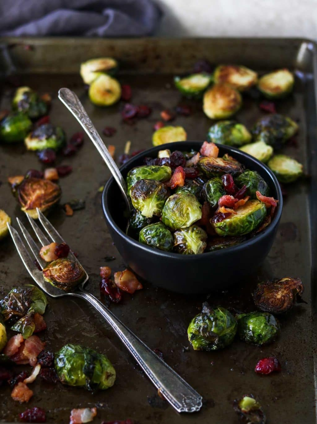 roasted brussels sprouts in a black bowl with a fork, sitting on a sheet pan scattered with brussels sprouts and bacon