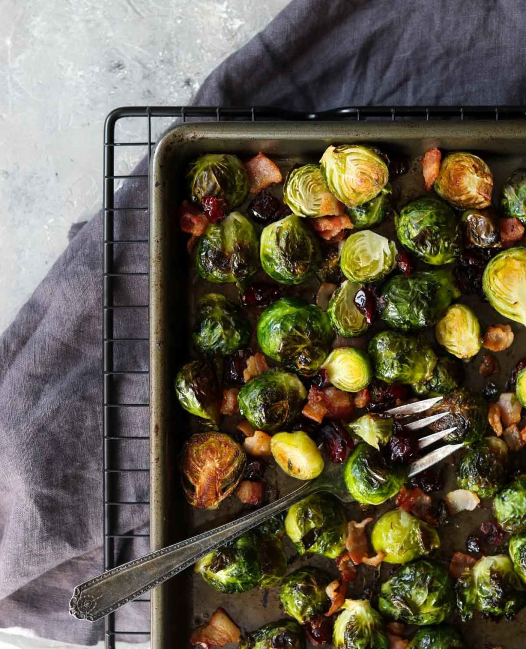 Oven roasted brussels sprouts on a sheet pan with a fork sitting on a black cooling rack