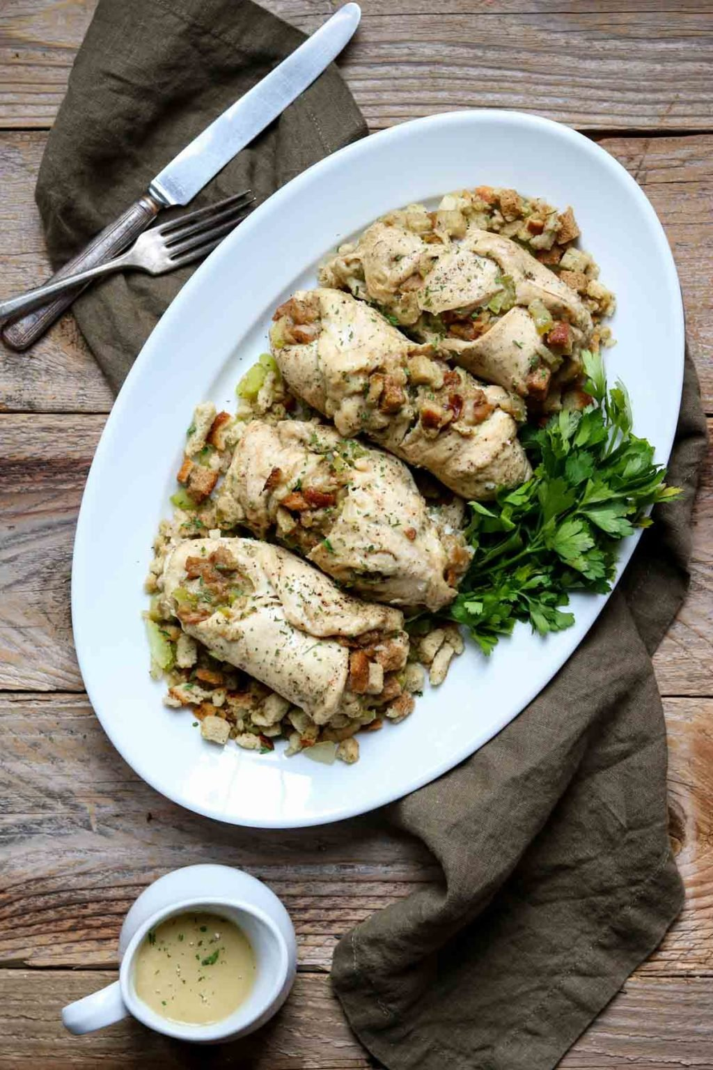Chicken with Stuffing on a white oval serving platter garnished with parsley, a knife and fork and gravy to the side