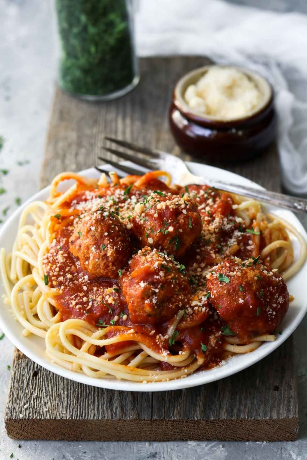 Turkey meatballs over spaghetti on a white plate on a wood board