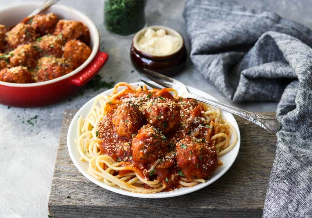 turkey meatballs over spaghetti and a red bowl of meatballs in the background