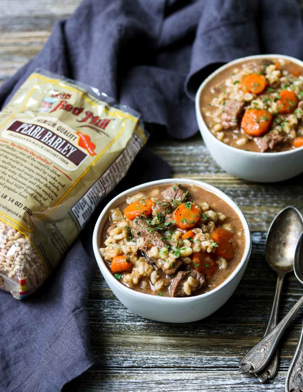 two bowls of beef and barley soup with a bag of bobs red mill pearl barley to the side