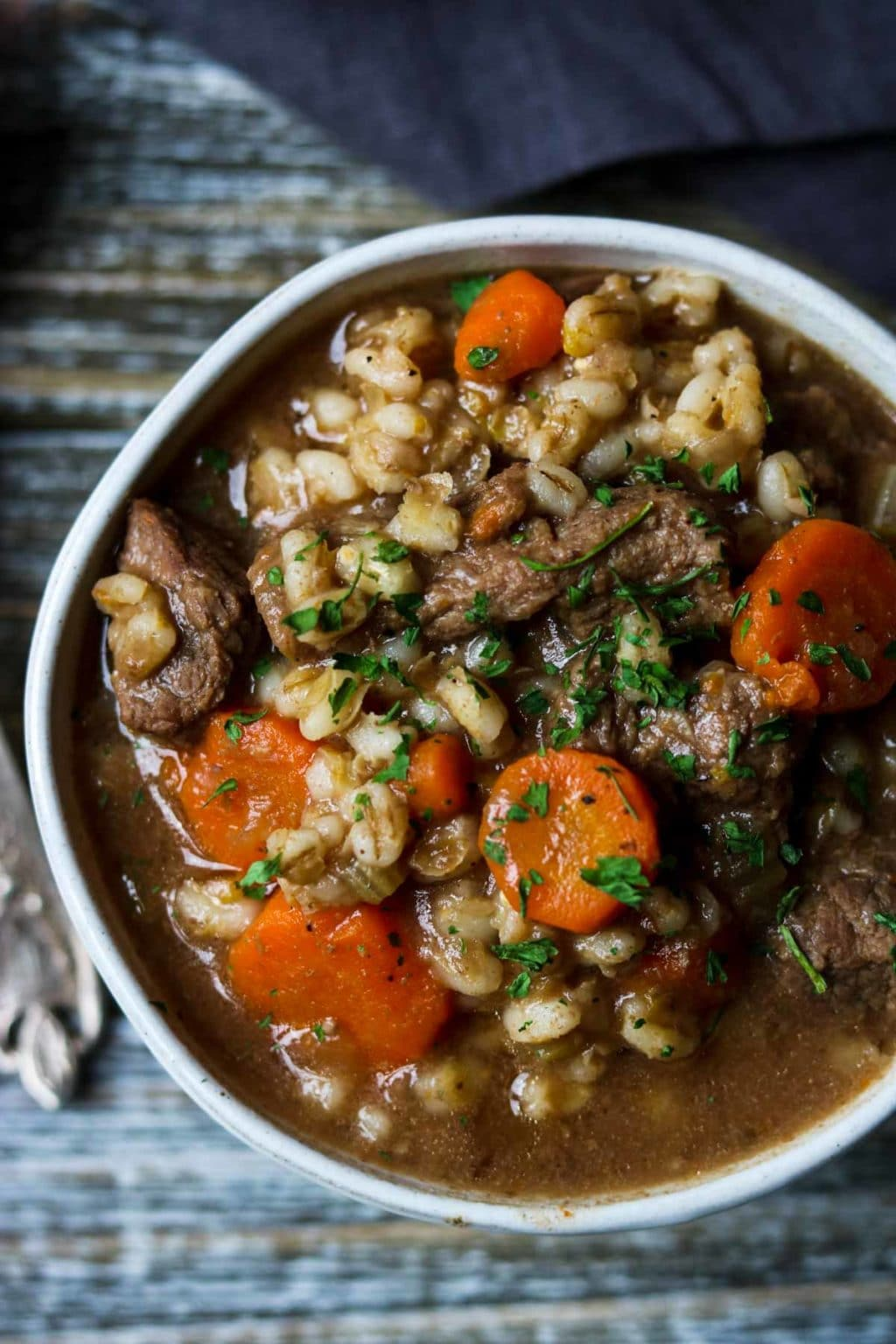a white bowl full of beef and barley stew on a wooden counter