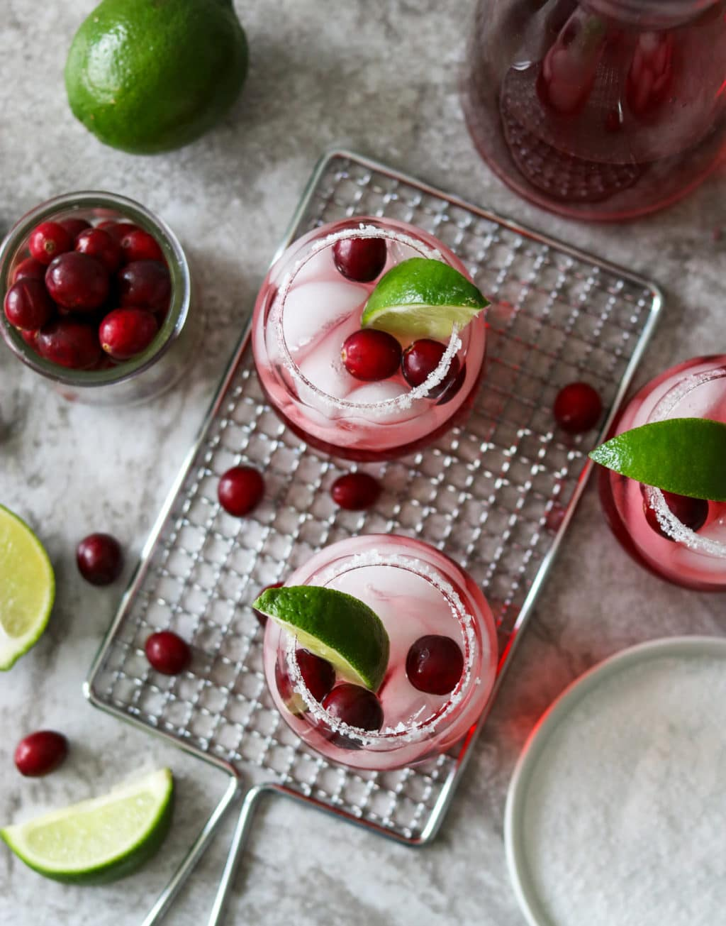 three cranberry ginger margaritas with limes and cranberries scattered on the counter