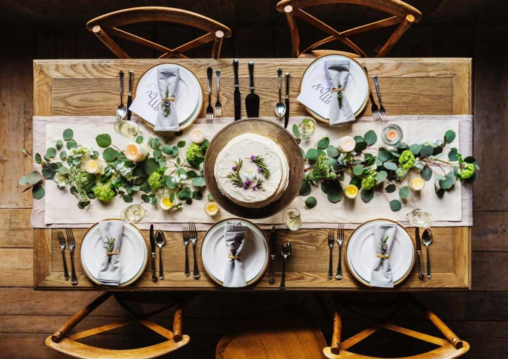wooden dinner table set with white plates and blue napkins, with a white table runner and greenery and candles