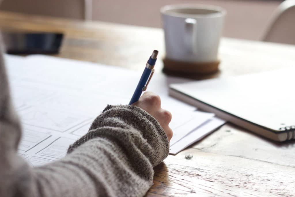 writing a list with a pen and a cup of coffee