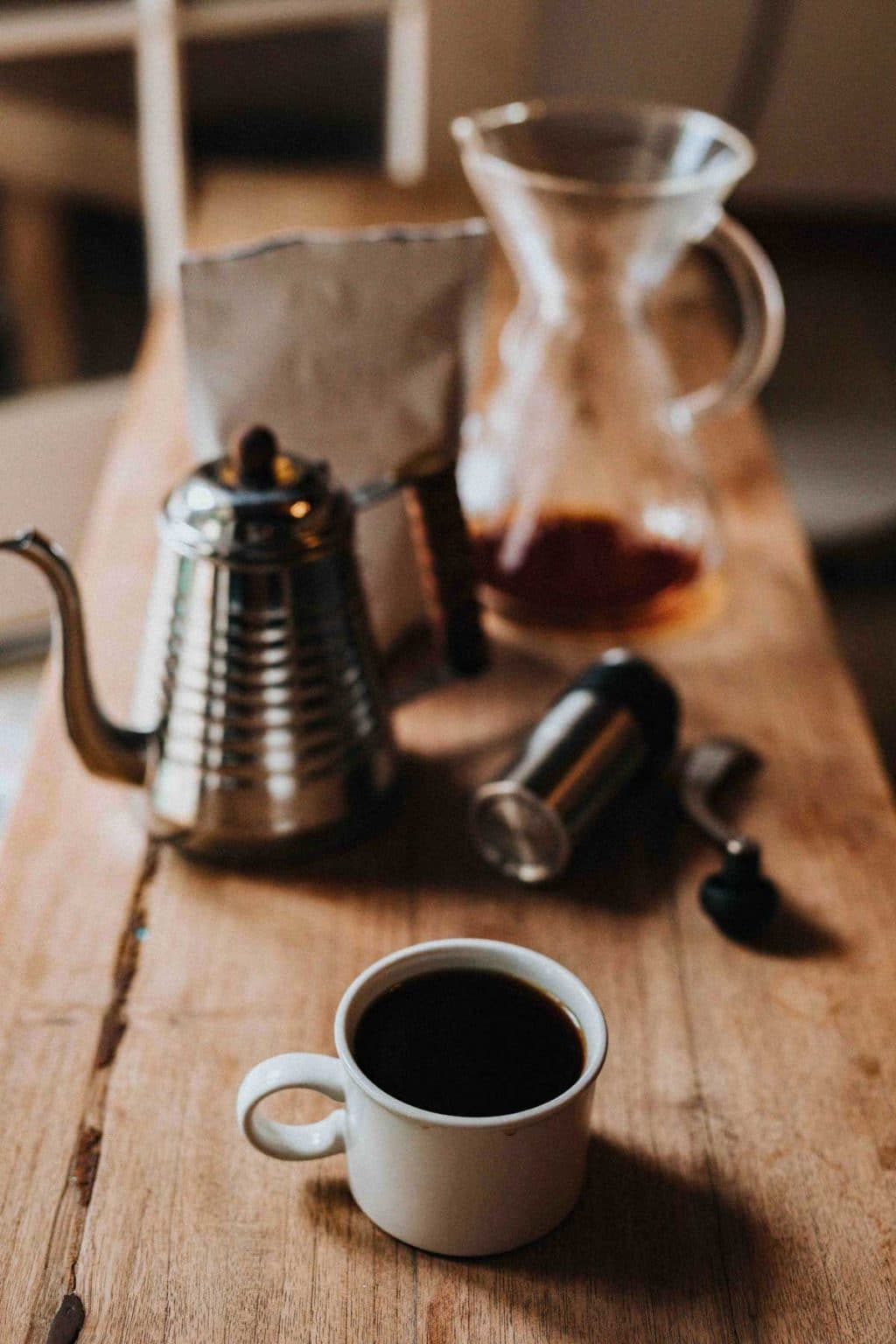 coffee in a white cup on a wooden table, coffee accessories in the background