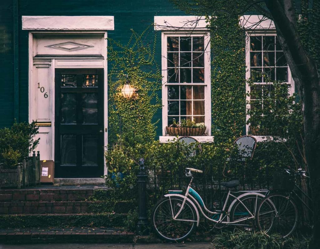 blue house with a black and white door and a blue bike leaning on a fence
