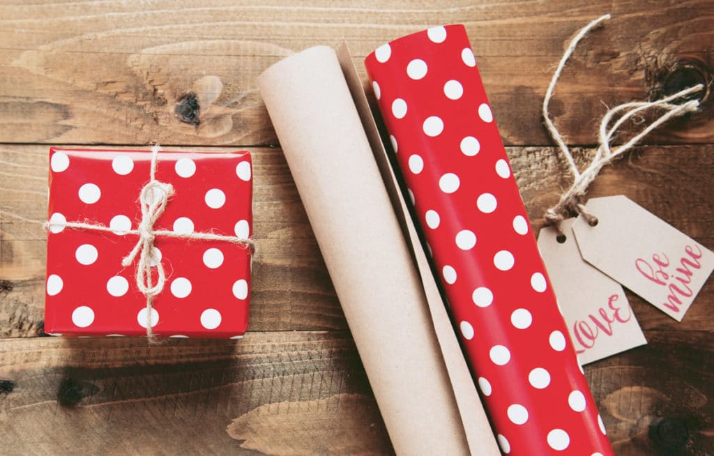 a gift wrapped in red wrapping paper with white polka-dots