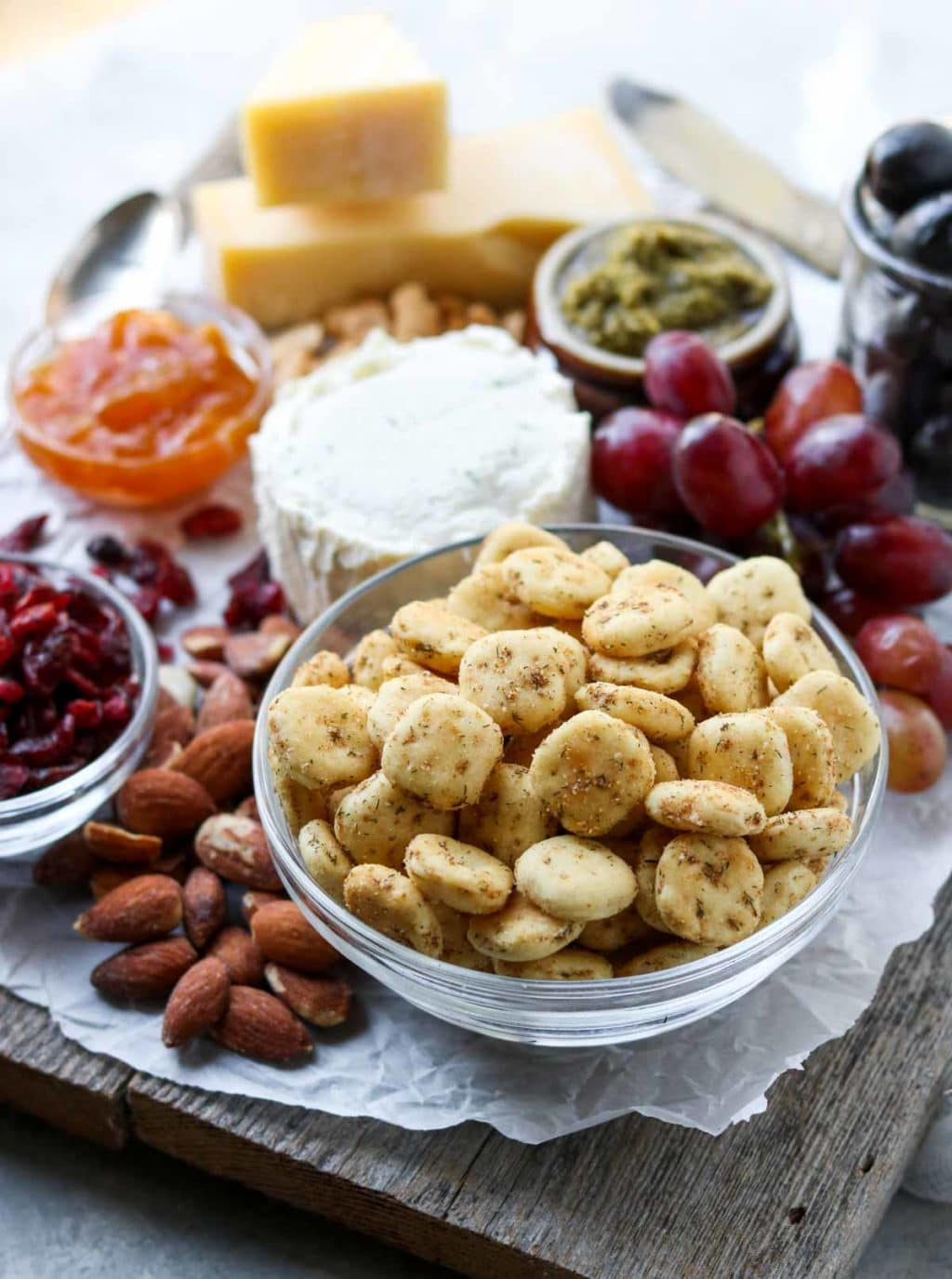 a cheese, nut and fruit board with seasoned oyster crackers