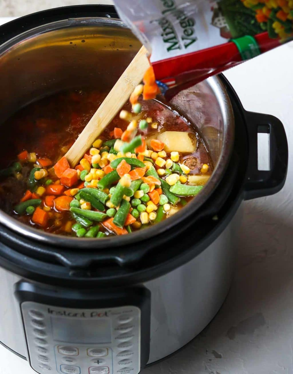 Frozen Mixed Vegetables being poured into the instant pot