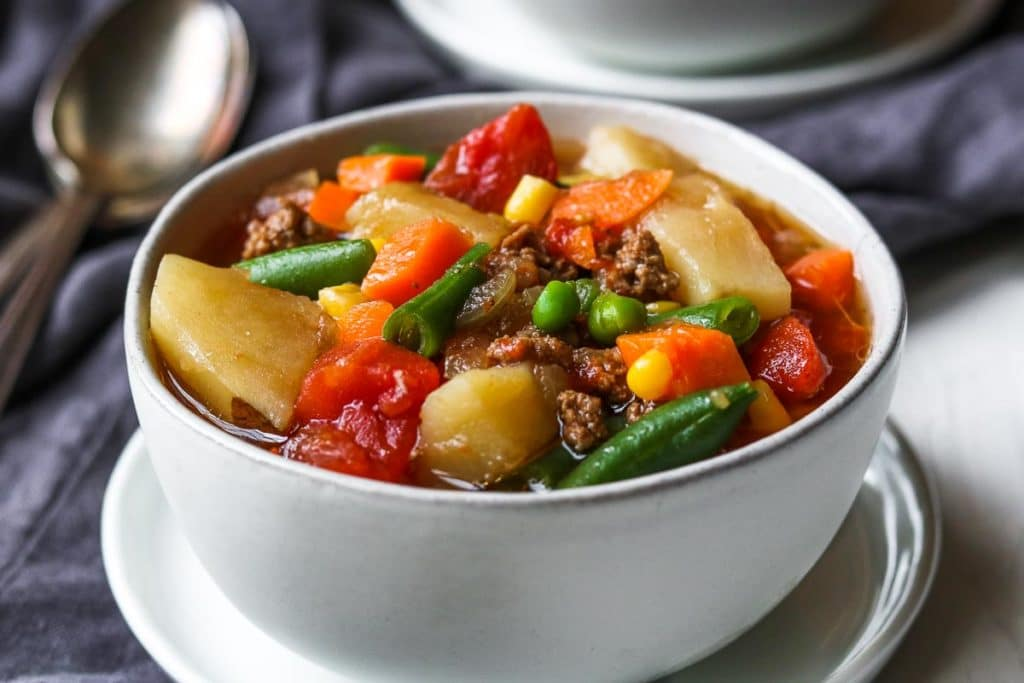 a white bowl of easy instant pot hamburger and vegetable soup- potatoes, tomatoes, beef, peas, corn, carrots, and green beans.