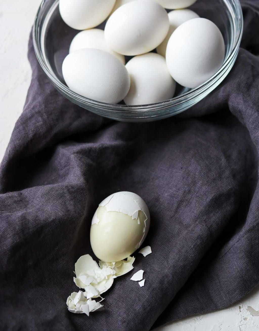 A bowl of hard boiled eggs cooked in the instant pot and one egg half peeled