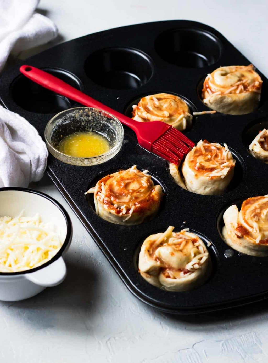 Pizza Roll Ups in a cupcake pan, topped with garlic butter