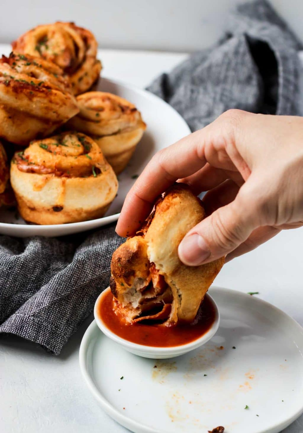 Pizza Roll Up being dipped in marinara sauce