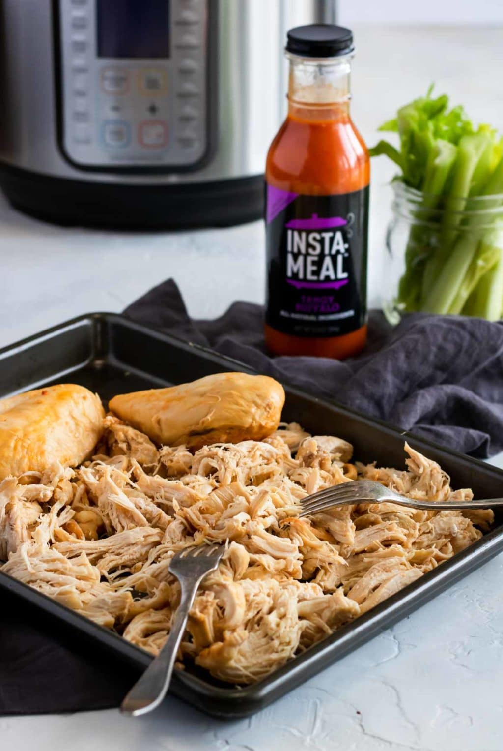 chicken shredded in a sheet pan with buffalo sauce in a bottle and the instant pot