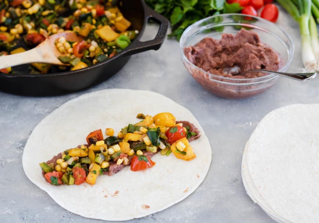 making veggie enchiladas in flour tortillas