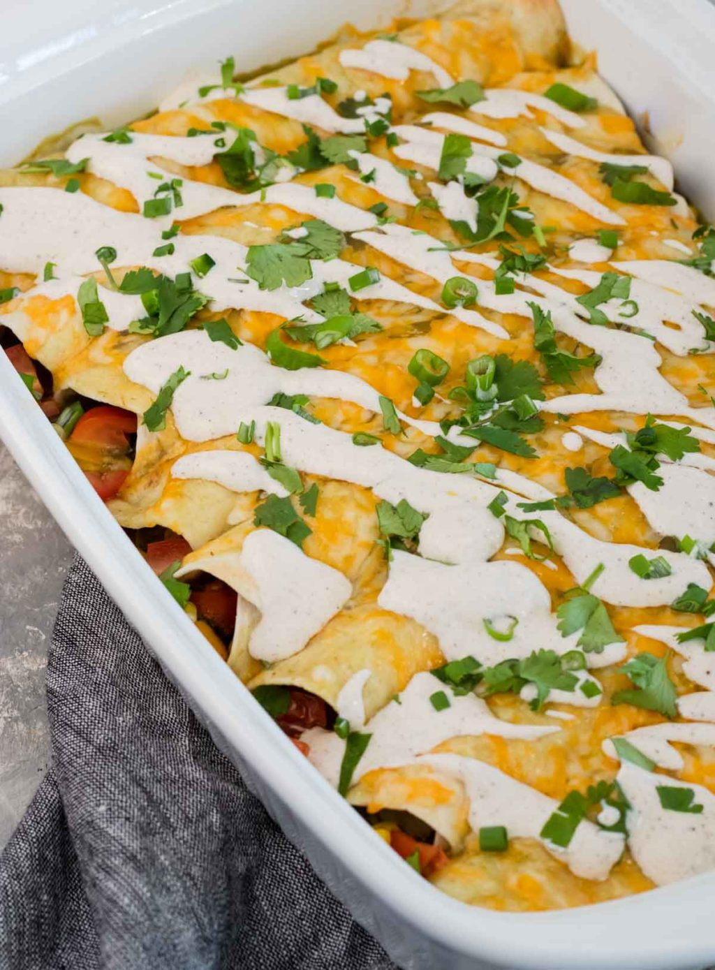 Veggie Enchiladas topped with Chili Lime Crema in a white glass baking dish