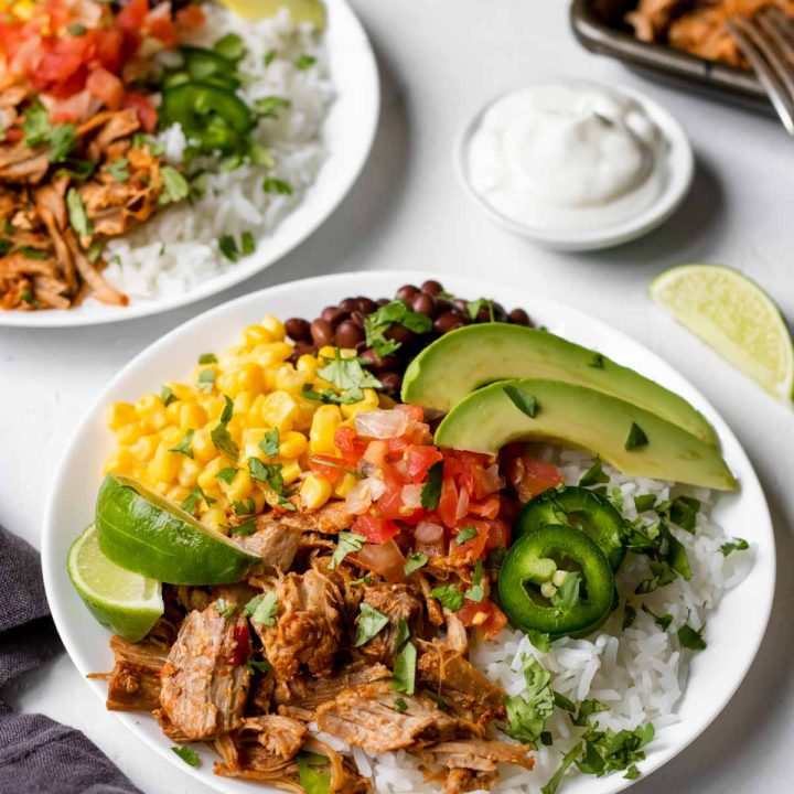 Carnitas burrito bowl garnished with cilantro, limes, avocado.
