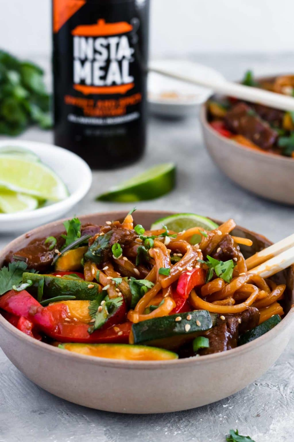 Instant Pot Teriyaki Beef Noodles in a bowl with an Instant Pot Sauce bottle in the background and a bowl of limes