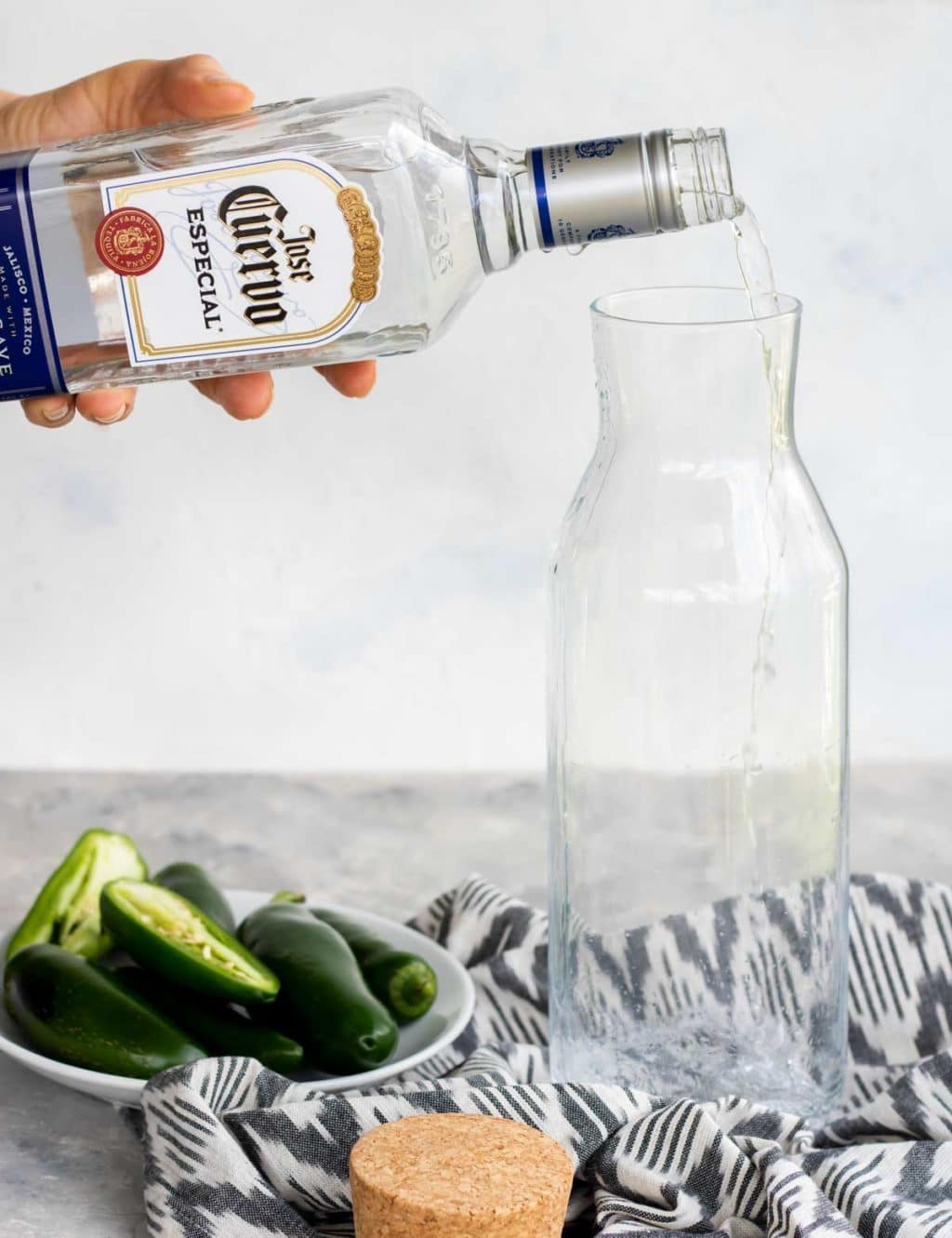 Pouring a bottle of silver tequila into a glass container with a bowl of jalapenos to the side