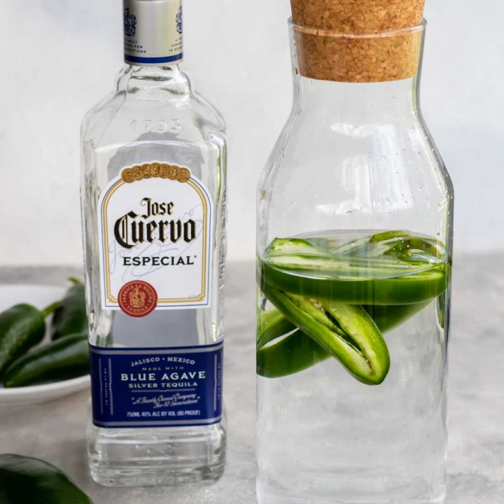 Making silver jalapeno tequila at home in a glass jar, jose cuervo silver tequila and a bowl of jalapenos