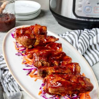 Instant Pot Boneless Pork Ribs on a white plate with an electric pressure cooker in the background