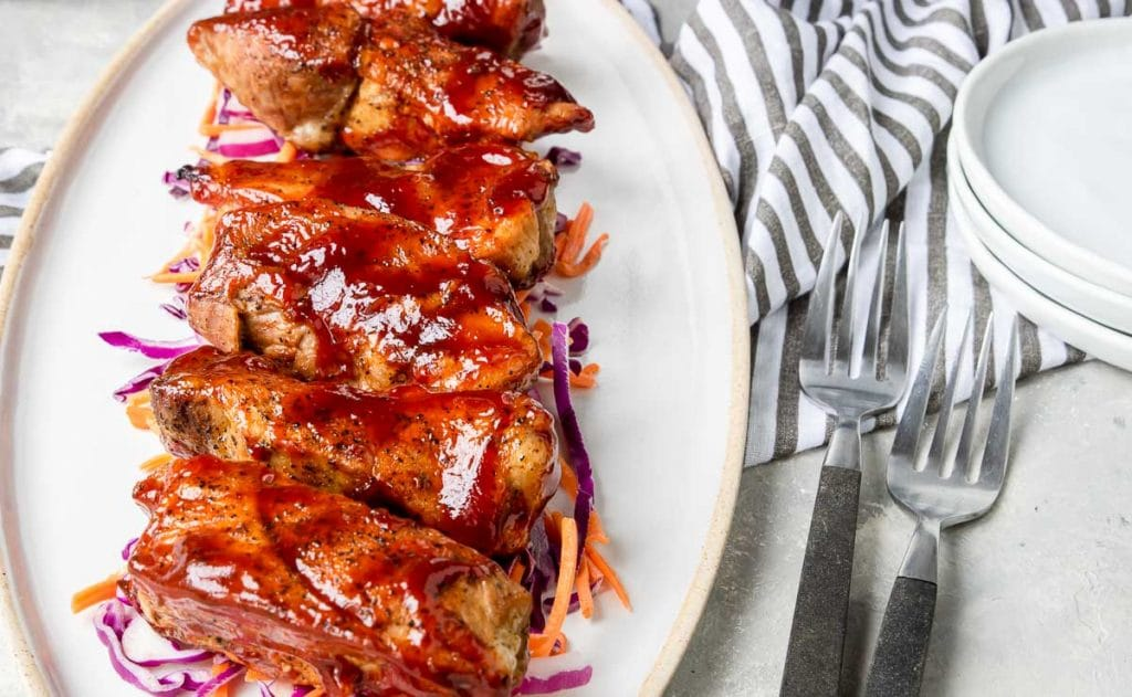 Instant Pot Country Style Ribs coated with bbq sauce on a white plate over coleslaw