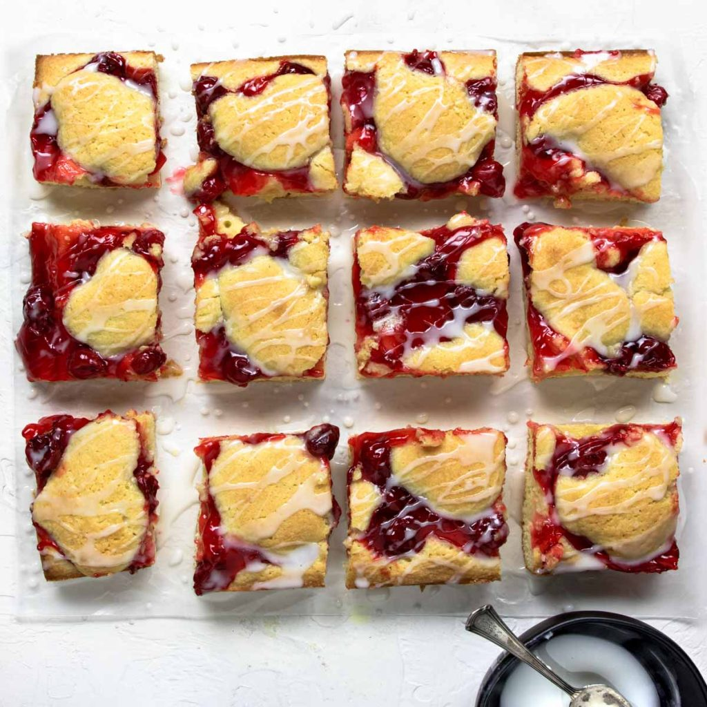 Homemade cherry Pie Bars cut into squares and laid on parchment paper, drizzled with frosting glaze