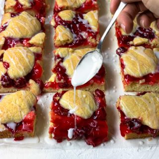 Easy cherry pie bars cut into squares and being drizzled with powdered sugar glaze