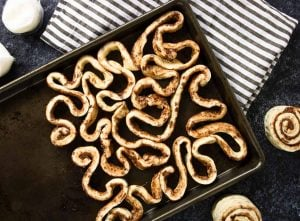 Cinnamon rolls strips coiled and twisted on a baking sheet - looks like intestines