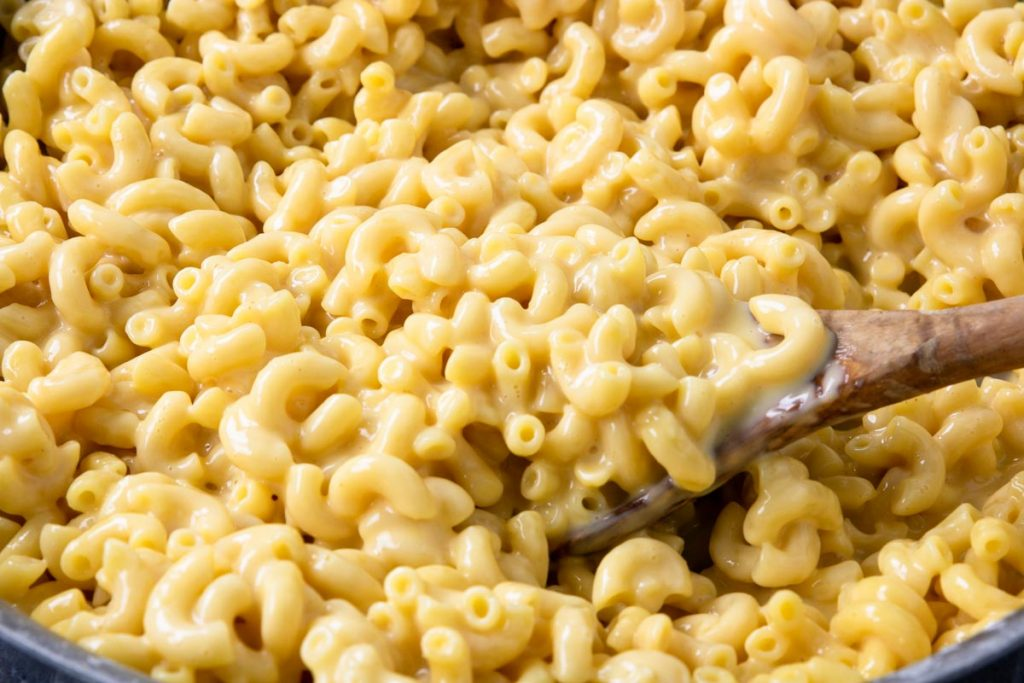 skillet mac and cheese in a pan with a wooden spoon