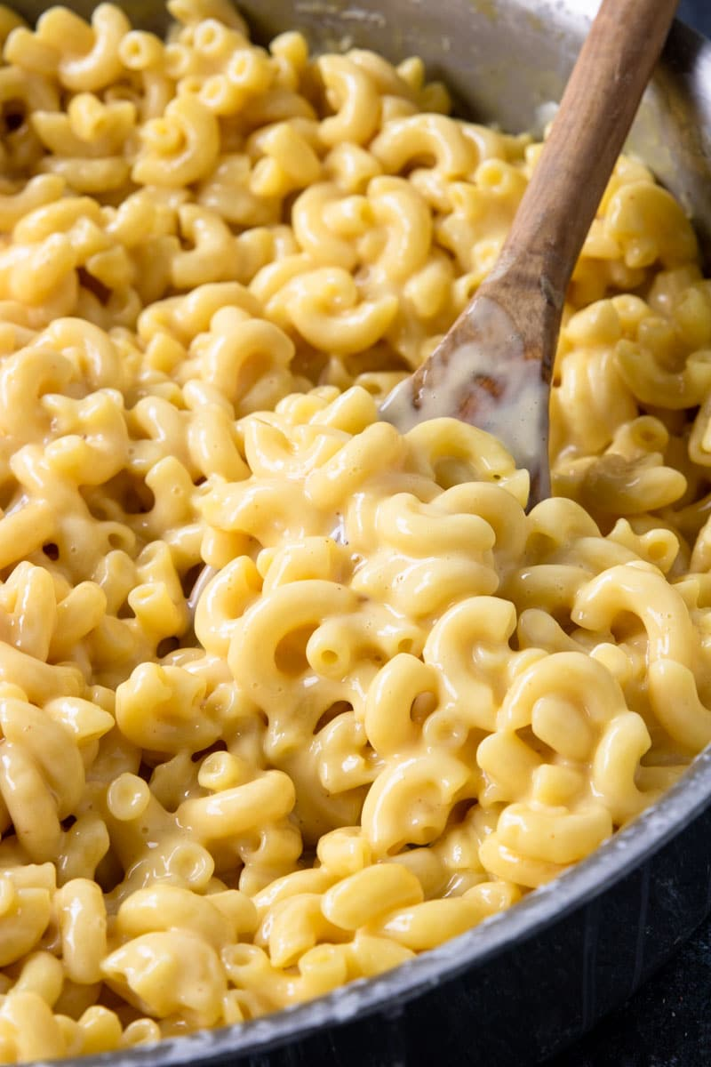 Skillet Mac and Cheese looking creamy and cheesy on a wooden spoon