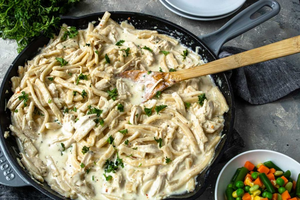 Creamy Chicken and Noodle recipe made in a large grey skillet, mixed veggies to the side