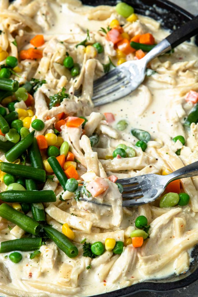 Creamy Chicken and Noodles in a skillet with mixed veggies added on top