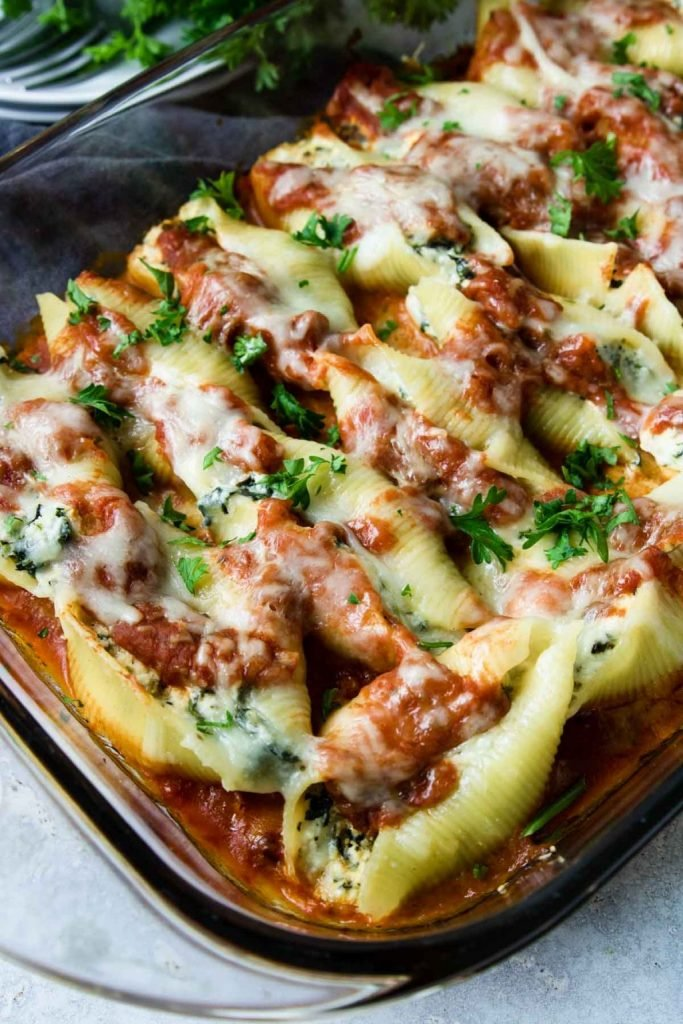 Ricotta and Spinach Stuffed Shells cooked in a glass 9x13 dish topped with cheese and sauce