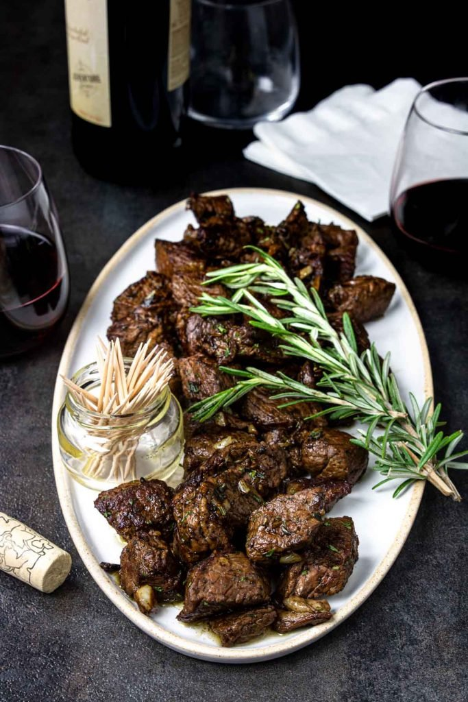Steak Bites with a garlic butter on a white plate, garnished with rosemary. A cup of toothpicks for serving as an appetizer.