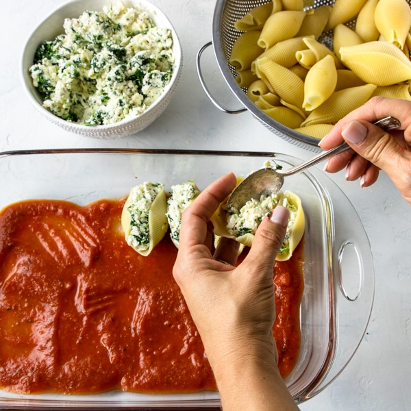 Step three filling the pasta shells with the ricotta and spinach filling, being layed into a prepared baking dish
