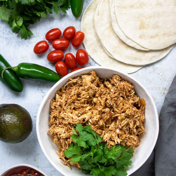 shredded chicken in a bowl with taco fixing around