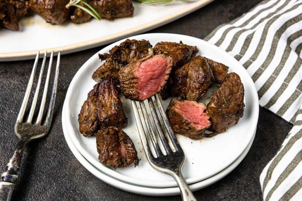 Garlic Steak Bite cut in half showing a medium rare cook