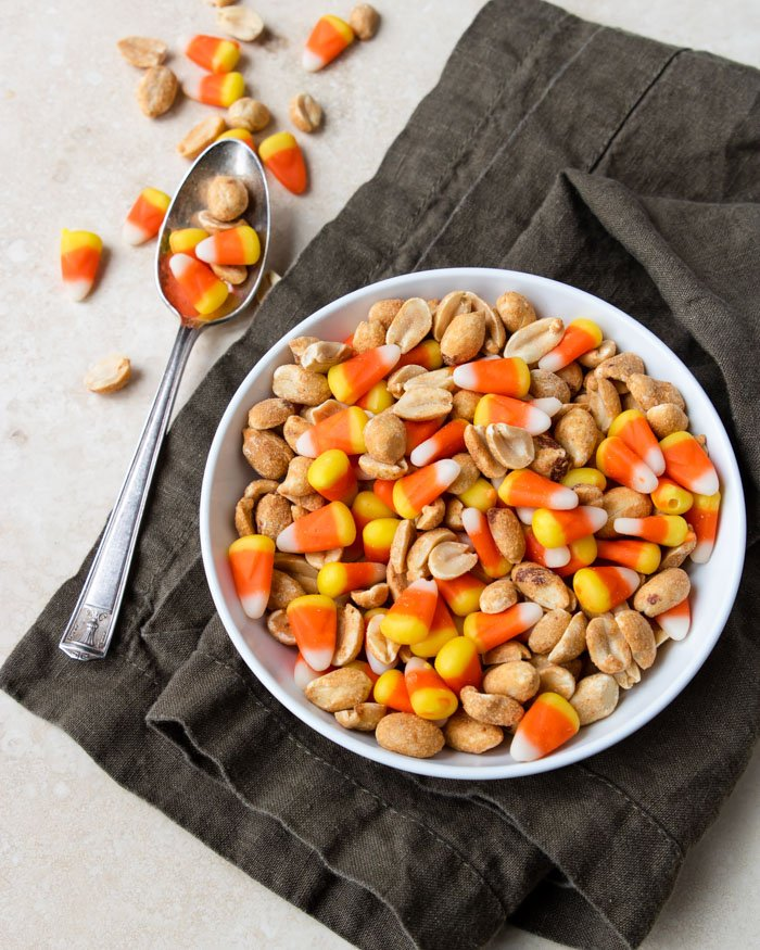 Candy Corn and Peanuts mixed in a white bowl