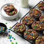 Chocolate cookies with M&M's on a cooling rack- pinterest text over top